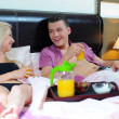 Happy young couple eating breakfast in bed — Stock Photo #27131377