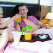 Happy young couple eating breakfast in bed — Stock Photo #27131379