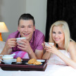 Happy young couple eating breakfast in bed — Stock Photo #27131395