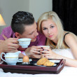 Happy young couple eating breakfast in bed — Stock Photo #27131403