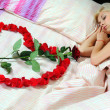Woman lying in bed with a rose in the form of heart — Stock Photo