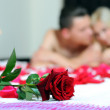 Rose on the bed, on the background of young couple — ストック写真