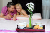 Smiling young couple together getting ready to enjoy breakfast in bed — ストック写真