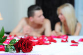 Rose on the bed, on the background of young couple — Stock Photo