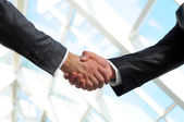 Businessman giving a handshake to close the deal — Stock Photo