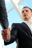 Business man giving a handshake to close the deal — Stock Photo