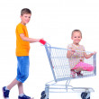 Two children - girl and baby - with shopping cart in supermarket — Foto de Stock