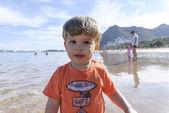 Criança brincando na praia com balde vermelho — Fotografia Stock