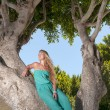 Beautiful young woman sitting on a tree trunk — Stock Photo #48961585