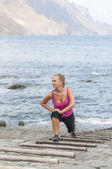 Healthy young woman running on the beach — Stock Photo