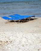 Sun loungers or beds on sandy beach — Stock Photo