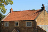 Brick house with red roof tiles — ストック写真