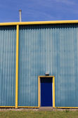 Blue and yellow warehouse building — 图库照片