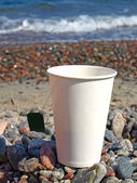 Paper cup on the pebbles — Stock Photo