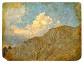 Retro postcard with a picture of mountains and clouds. — Foto de Stock