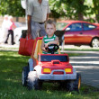 Blond boy driving a toy car — Stock Photo