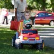 Stock Photo: Blond boy driving a toy car