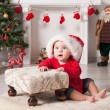 Foto Stock: A young baby is staring at the camera wearing a Santa Christmas hat.