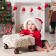 Stockfoto: A young baby is staring at the camera wearing a Santa Christmas hat.