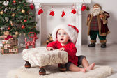 A young baby is staring at the camera wearing a Santa Christmas hat. — Stock Photo