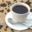 Cup with coffee beans - Stockfoto