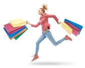 Woman running with shopping bags — Stock Photo