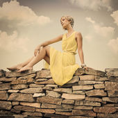The girl is sitting on a stone wall — Stock Photo