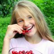 Happy girl eating cherry — Stock Photo #12477444