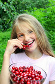 Happy girl eating cherry — Stock Photo