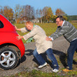Senior couple push the broken car — Stock Photo