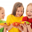 Kids eating cake with cream and fruits — Stock Photo
