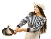 Young girl sailor cooking fishes — Stock Photo