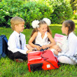 Schoolboy and schoolgirls in the park — Stock Photo