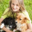 Happy child playing with dogs — Stock Photo