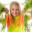 Beautiful little girl holding carrots — Stock Photo