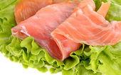 Sliced salmon fish on green salad — Stock Photo