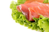 Sliced salmon fish on green salad isolated on white background — Stock Photo