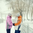 Snowball fight. Winter couple having fun playing in snow outdoor — Stock Photo #43820081