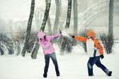 Snowball fight. Winter couple having fun playing in snow outdoor — Stock Photo