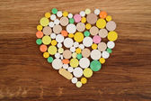 Heart of different pills on a wooden background — Stock Photo