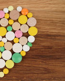 Half a heart of different pills on a wooden background — Foto de Stock