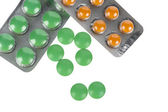 Green and orange pills in blisters on white background — Stock Photo