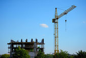 建物クレーンと青い空を背景に建設中の建物 — ストック写真