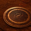 And electric service manhole cover shinning in soft copper tone under the street lights at night — Stock Photo #36682353