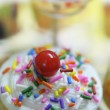Close-up of a delicious cupcake with sweet creamy white icing, colorful sprinkles and a red cherry on top - very shallow depths of field — Stockfoto #36683303