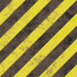 Old grungy yellow hazard stripes on a black asphalt - seamless texture perfect for 3D modeling and rendering — ストック写真
