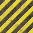 Old grungy yellow hazard stripes on a black asphalt - seamless texture perfect for 3D modeling and rendering — Foto Stock