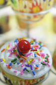 Close-up of a delicious cupcake with sweet creamy white icing, colorful sprinkles and a red cherry on top - very shallow depths of field — Stock Photo