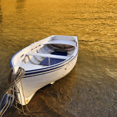 A small row boat beached on the shore at sunset - Cadaques, Spain — Fotografia Stock