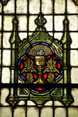 Stained Glass window with a chalice and sun inscribed IHS (Iesus Hominum Salvator, In His Service) — Stock Photo